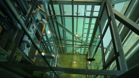 Lift moving upwards and arriving on the floor, view through glass elevator shaft Footage