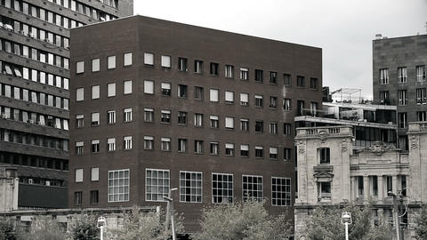 Old historical building surrounded by industrial architecture, black-and-white Footage