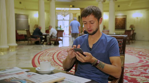 Young man looking up places of interest at morning coffee and smiling at camera Live Action