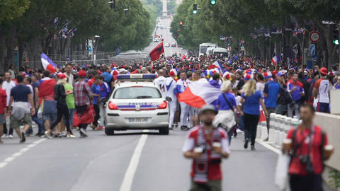 Police car driving down crowded street with football fans, French supporters Footage