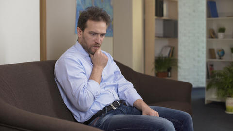Desperate man sitting on couch and thinking about money loss, negative emotions Footage