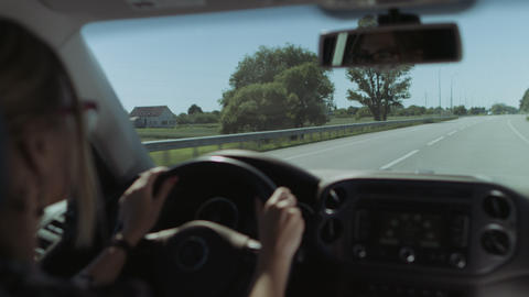 Female driver driving car on freeway on road trip Footage