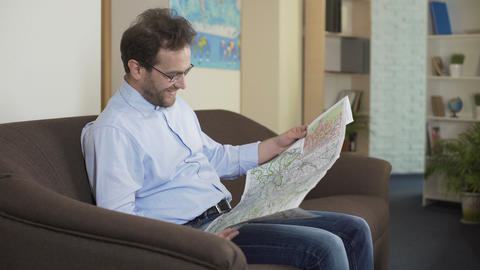 Happy male looking at the map and planning his summer trip, traveling and joy Footage