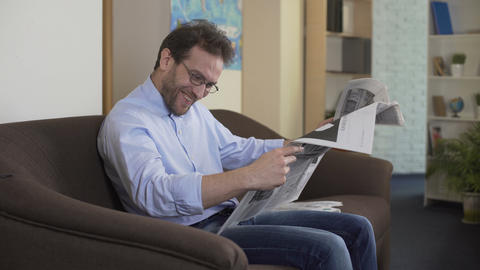 Pleased man reading anecdotes in newspaper, free time and relaxation at home Footage