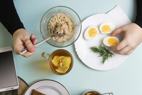 Healthy breakfast. Freelancer, woman, breakfast, working, top view, copy space フォト