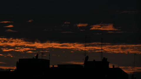 Time lapse - Dark red sunset over city with dramatic clouds. Day to night Footage