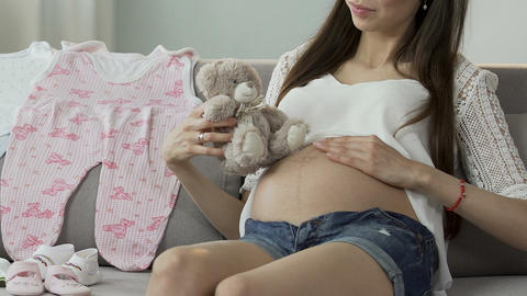 Mother-to-be holding teddy bear next to belly, sweet pregnancy, tenderness Footage