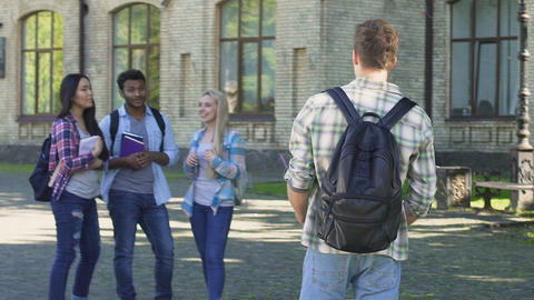 Student walking to best friends waiting him near university, students hugging Live Action