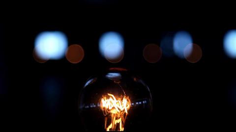 Flickering light bulb on black background Footage