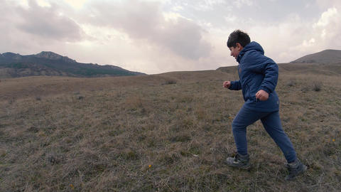 A boy on field with tall grass run to horizon with mountains. Slow motion video Footage