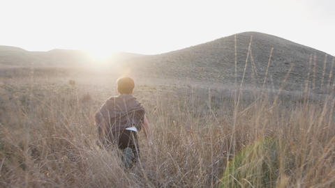 A boy with a sword runs to the horizon at sunset in grass. Slow Motion video GIF
