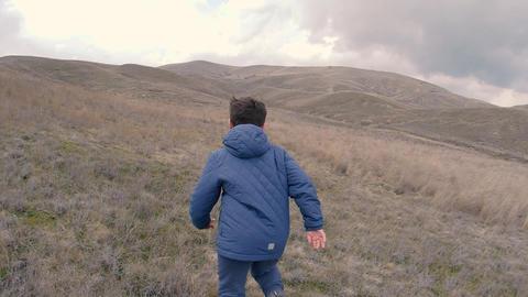 A boy runs in grass to horizon Footage