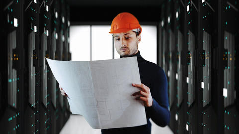 A handsome man in safe helmet read blueprints with large system servers in Live Action
