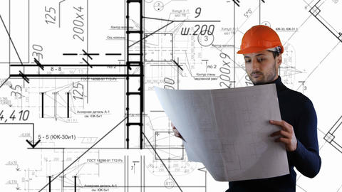 A man in safe helmet read blueprints in the flying out building schemes Live Action