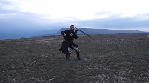 Knight fencing his sword against the backdrop of the mountains at morning Live Action
