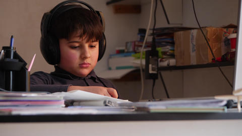 A boy in big headphones is busy be reading Footage