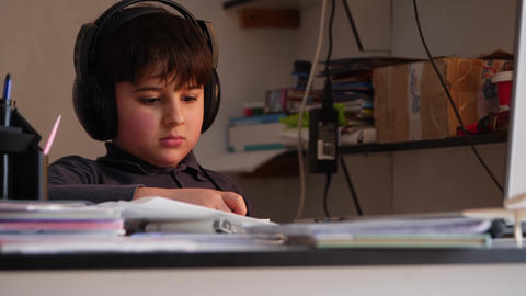 A boy in big headphones is busy be reading Stock Video Footage