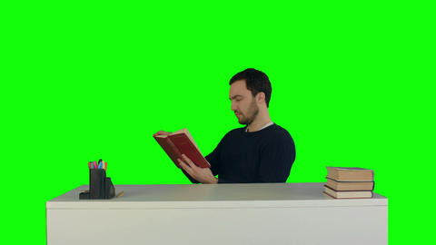 Portrait of a male student reading a book on a Green Screen Footage