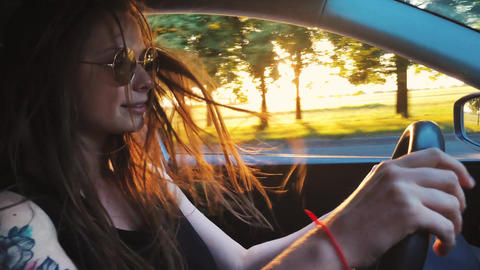 Beautiful cheerful woman driving a car, beautiful scenery and sunset outside Footage