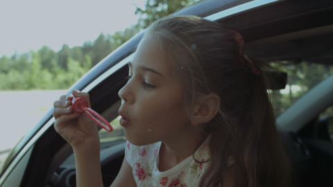 Adorable child blowing soap bubbles in the car Footage