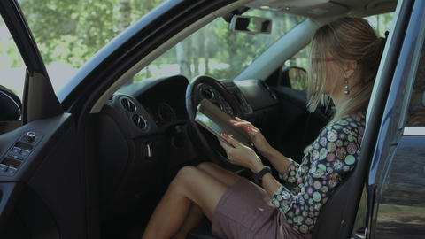 Charming woman networking with tablet in the car Footage