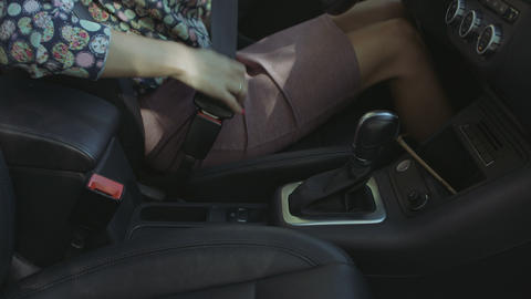 Female driver buckles up seat belt in the car Live Action