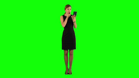 Young adult woman applying lipstick herself on a Green... Stock Video Footage