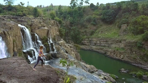 girl does yoga on rocky land against waterfall streaming from cliff Archivo