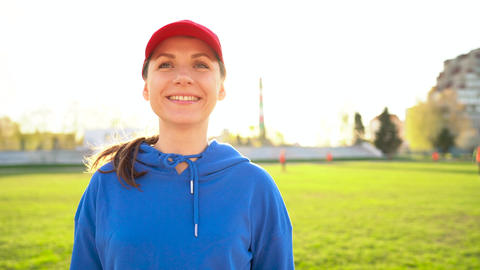 Portrait of a sporty smiling girl in a stadium at sunset Stock Video Footage