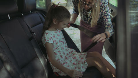 Caring mother fastening girl with seat belt in car Live Action