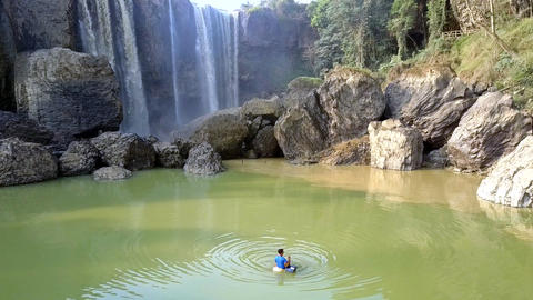 foamy waterfall streams from height boy fishes in pond Footage