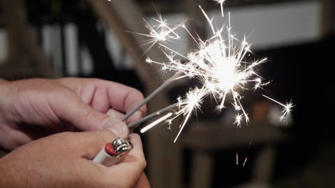Close up of a man using a disposable lighter to ignite a sparkler at night in Footage