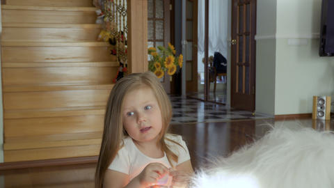 Adorable little girl sit on soft toy on the floor at home Footage