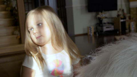 Cute little girl sit on big soft toy and touching her hair flirting with camera Footage