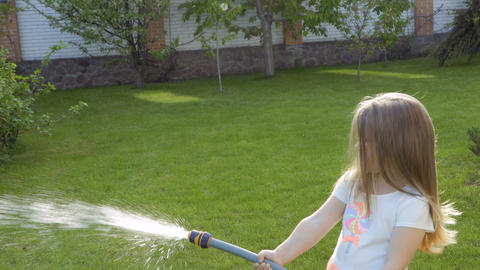 Cute little girl water a flower bed from a hose Footage