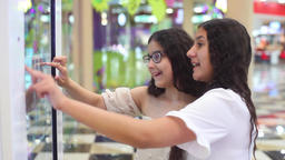 Two girls use the interactive panel in the mall. girls choose the goods with the Footage