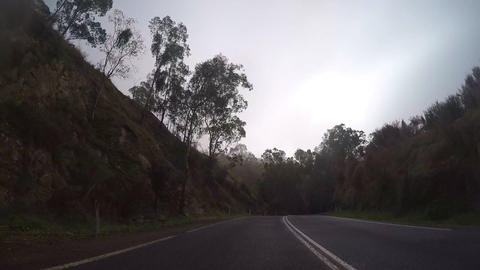 Vehicle POV, driving along winding mountain country road through early morning Footage