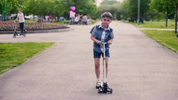 The boy skates on a scooter in a park with people in summer sunny weather having Footage