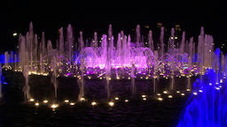 Bright colorful water in dancing fountains of ultraviolet colors at night Footage