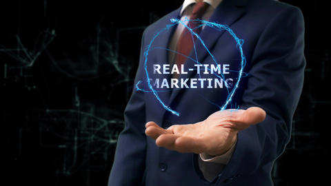 Businessman shows concept hologram Real-time marketing on his hand Live Action