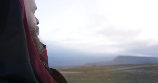 Face of a man with a beard and in a hood in profile A man looking towards the Footage