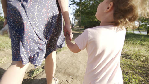 Mother holds the hand of small child's daughter while walking Live Action