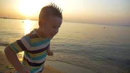 Child making angry face on the beach at sunset Footage