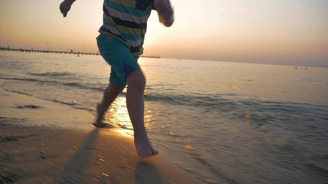 Child running barefoot along the sea at sunset Footage