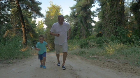 Grandfather and grandson jogging in the forest Footage