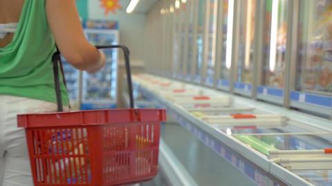 Woman walking in fridge section of supermarket Footage