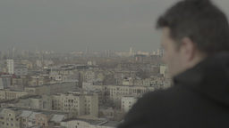 A man watches a large city during the day underneath it Footage