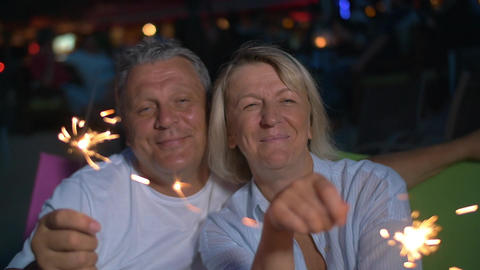 Happy senior man and woman with sparklers Footage