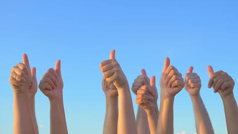 Hands up with thumbs-up against blue sky Footage