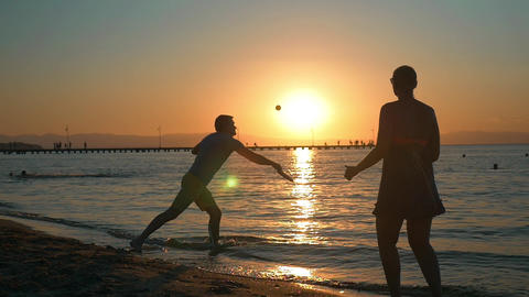 Couple playing tennis on the beach at sunset Footage